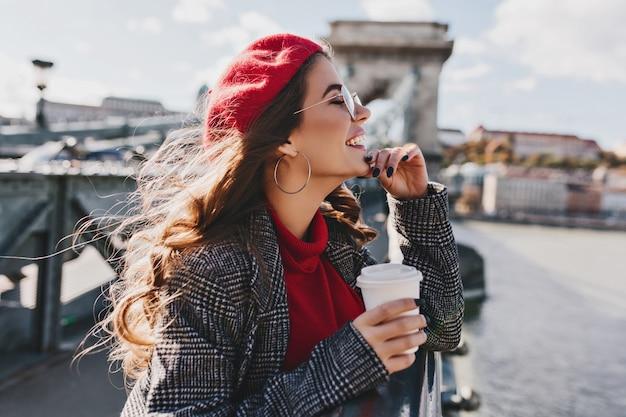 暖かい風の強い日に街の景色を楽しむ赤い帽子ののんきな白人女性 無料写真