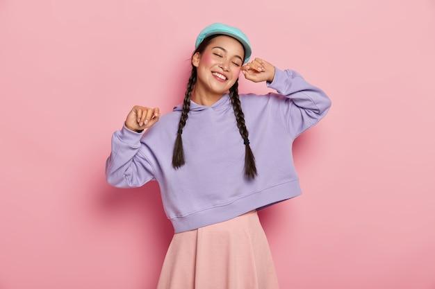 のんきな陽気なミレニアル世代のアジアの女性は手を上げ続け、ピンクの壁に向かって踊り、目を閉じて、好きな音楽から喜びを得る 無料写真