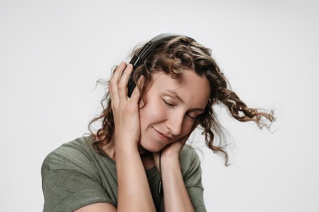 のんき陽気な若い巻き毛の女性は彼女のヘッドフォンで手で好きな音楽を聴きます Premium写真