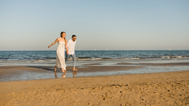 Carefree couple holding each other's hand running on the seashore Free Photo