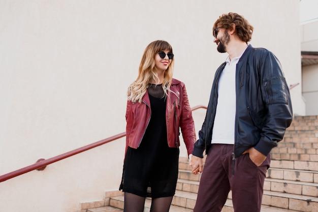 Беззаботная влюбленная пара гуляет по городу в городском стиле. выразительная блондинка с ее красивым парнем весело. весенний стильный наряд. Бесплатные Фотографии