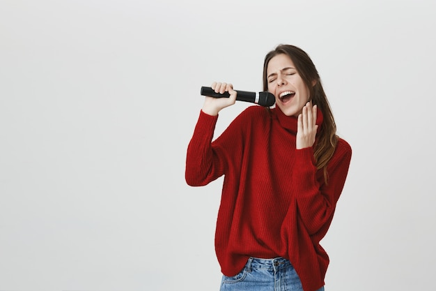 Carefree cute woman singing karaoke in microphone Free Photo