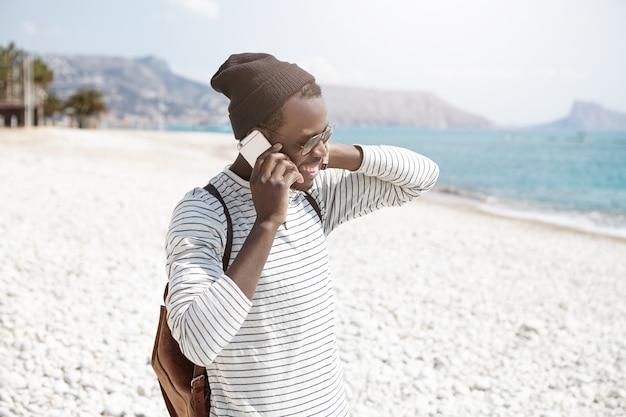 夏の海でリラックスして小石のビーチを歩きながらスマートフォンで会話している流行の服を着たのんきな黒肌のヒップスター 無料写真