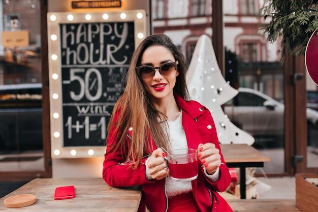 Ragazza spensierata con acconciatura lunga che beve il tè in street cafe Foto Gratuite
