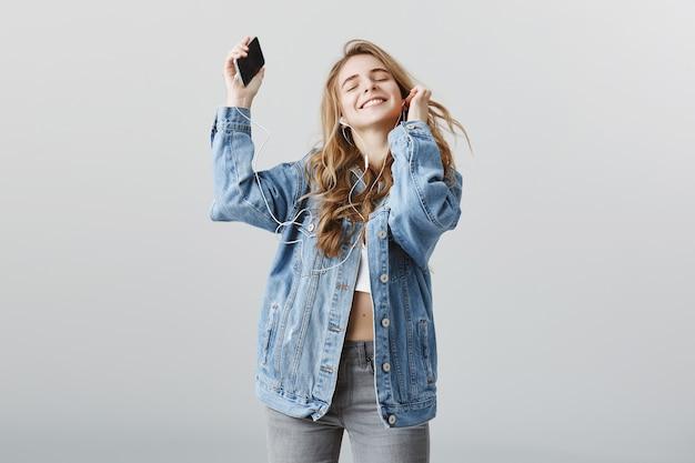 ヘッドフォンで音楽に合わせて踊るのんきな幸せなブロンドの女の子、うれしそうな笑顔 無料写真