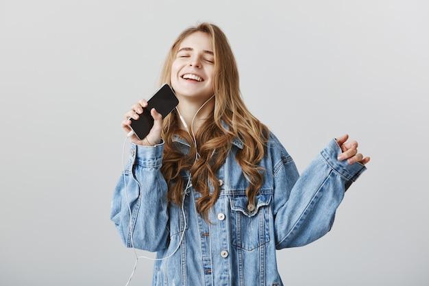 Carefree happy blond girl playing karaoke app on mobile phone, singing into smartphone in earphones Free Photo