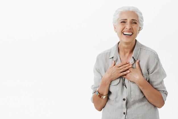 Беззаботная счастливая пожилая женщина с седыми волосами смеется и улыбается Бесплатные Фотографии
