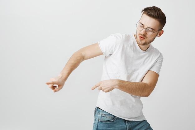 音楽を聴く、ワイヤレスイヤホンで踊るように左を指す屈託のない幸せな男 無料写真