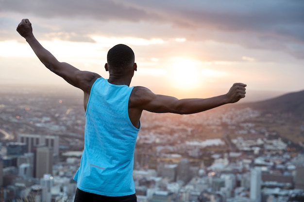 Carefree independent man with dark skin, stands back, stretches hands as holding world, feels freedom, wears blue casual vest, enjoys panoramic view with sunrise. recreation concept Free Photo