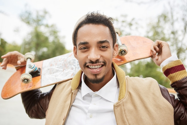 のんきな混血の男性スケボーダーがスケートボードを後ろで支え、幸せそうに笑う 無料写真