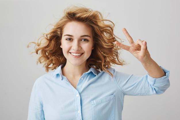 ピースサインを見せて笑顔の巻き毛の屈託のない楽観的な女の子 無料写真