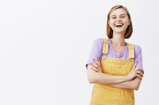 Беззаботная довольно смеющаяся девушка весело смотрит на белую стену Бесплатные Фотографии