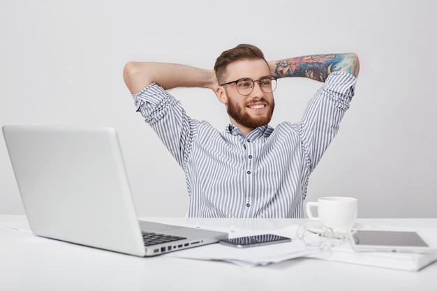 のんきなリラックスした創造的な男性労働者は、仕事の机に座って思慮深く脇を見ている間、身をかがめる 無料写真