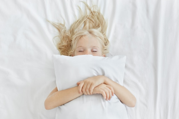 Беззаботная спокойная маленькая девочка лежит на белом постельном белье, обнимает подушку, имея приятные сны. белокурая девушка с веснушками, спать в постели после тратить весь день на пикник. спокойный ребенок Бесплатные Фотографии