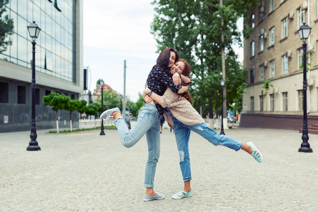 Carefree smiling sisters hugging and having fun together Free Photo