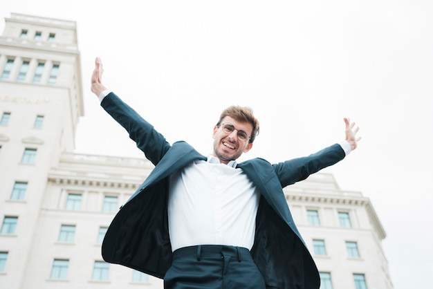 Carefree smiling young businessman standing in front of building raising his arms Free Photo