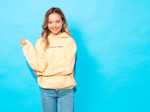 Carefree woman posing near blue wall in studio. positive model having fun Free Photo