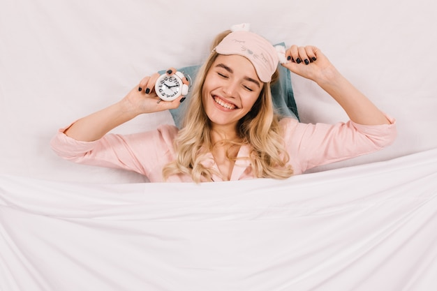 Беззаботная женщина с часами, лежа на подушке Бесплатные Фотографии