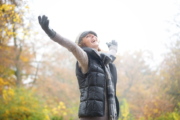 Carefree woman with outstreched arms in autumn Premium Photo