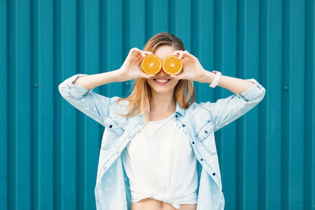 Carefree young beautiful girl using two halfs on oranges instead of glasses over her eyes Free Photo