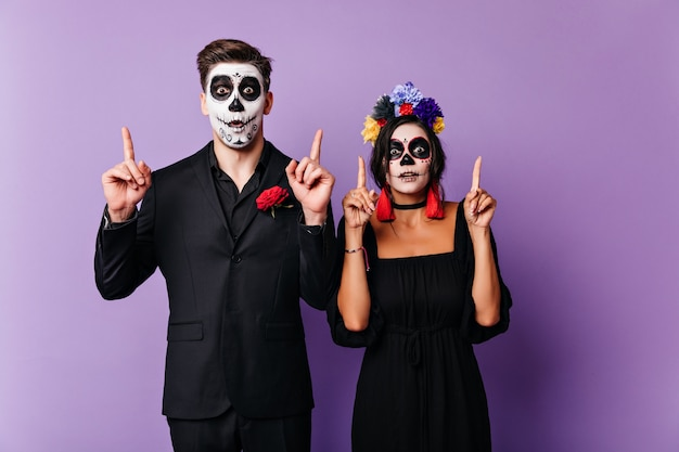 Carefree young people in zombie costumes making funny faces. european friends expressing amazement in halloween. Free Photo