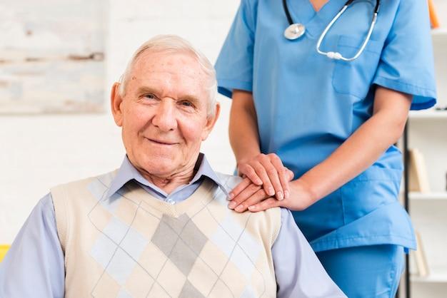 Caregiver holding old man's shoulder Free Photo