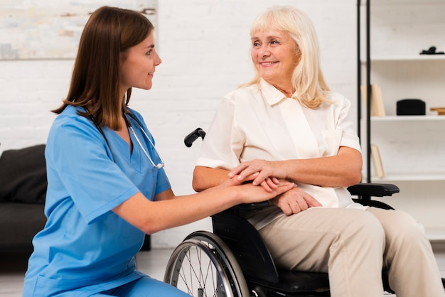 Caregiver taking care of woman in wheelchair Free Photo