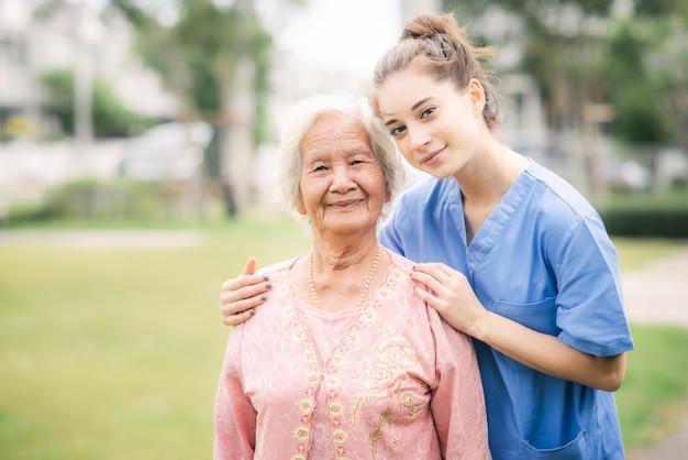 Caregiver with asian elderly woman outdoor Premium Photo