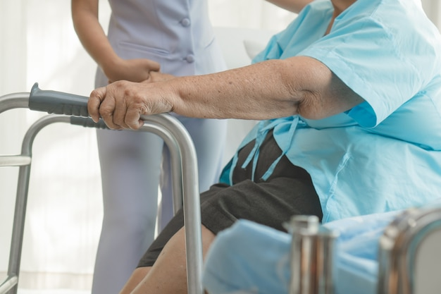 Caregivers help elderly to walk in the physical therapy.a Premium Photo