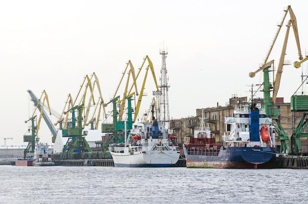 Грузовое судно и грузовой контейнер, работающие с краном на территории порта Premium Фотографии