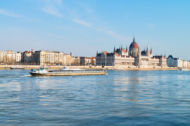 Cargo ship passes parliament building in central budapest Premium Photo