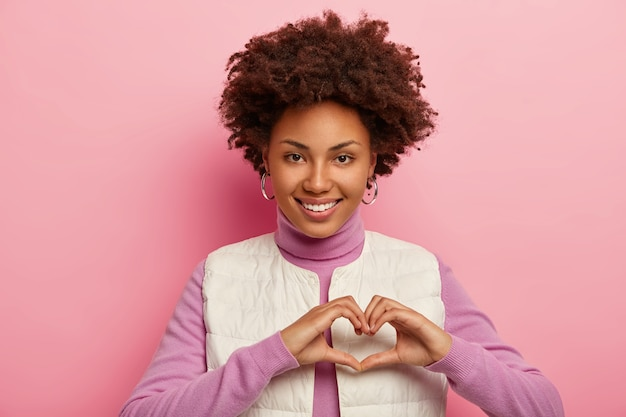 Caring african american lady shows heart gesture, expresses love, admiration and sympathy, smiles happily, shows white teeth, demonstrates affection, wears white vest. Free Photo