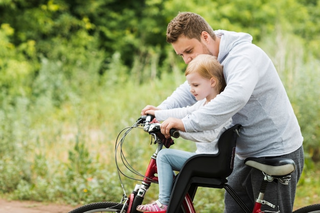 Caring father holding daughter on bike Free Photo