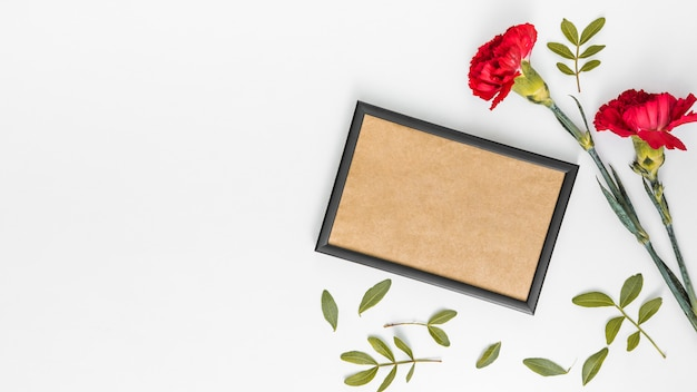 Carnation flowers with blank frame on table Free Photo