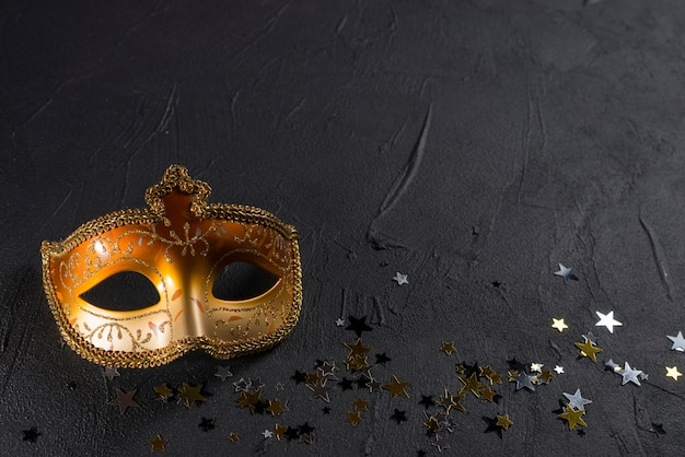 Carnival mask with spangles on black table Free Photo