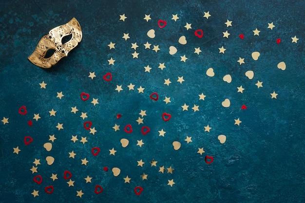 카니발 마스크와 골드 반짝이 색종이. 상위 뷰, 파란색 배경에 가까이 프리미엄 사진