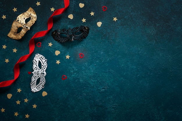Carnival masks and gold glitter confetti. top view, close up on blue background Premium Photo