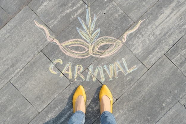Carnival written on gray sidewalk with women legs in yellow shoes Premium Photo