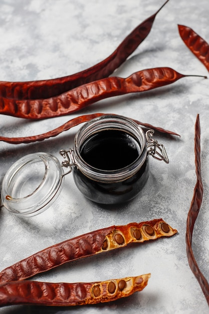 Carob syrup in glass jar with carob pods and seeds on light Free Photo