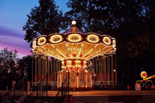 Carousel merry-go-round in amusement park at evening city Premium Photo
