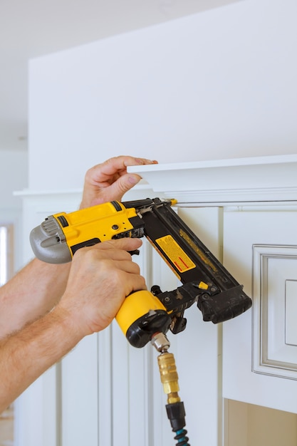 Carpenter brad using nail gun to crown moulding on kitchen cabinets framing trim, Premium Photo