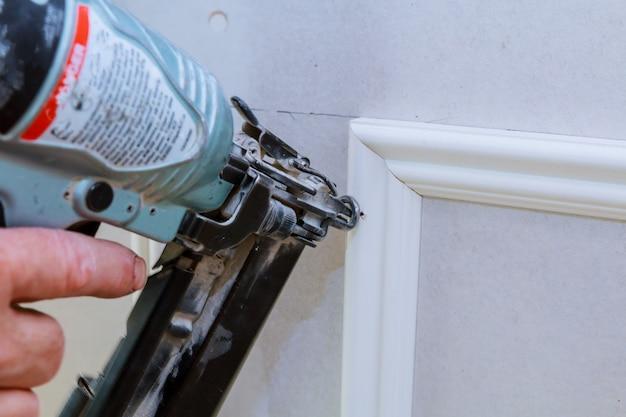 Carpenter Brad Using Nail Gun To Moulding Trim With The Warning Label That Power Tools Premium Photo