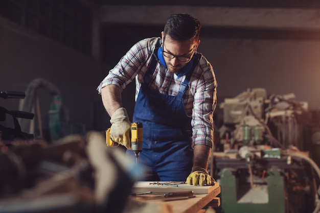 Carpenter drills a hole with an electrical drill Premium Photo