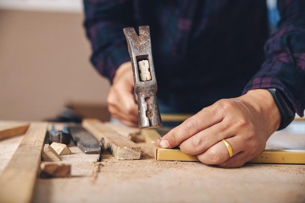 Плотник забил гвоздь. строительная индустрия, сделай сам. деревянный рабочий стол. Premium Фотографии