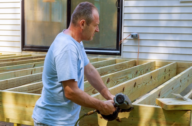 A carpenter hammering on a installing of wooden deck patio Premium Photo