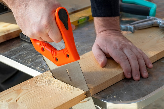 Carpenter hand with handsaw cutting wooden boards. Premium Photo