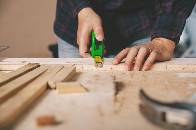 Карпентер держит рулетку на рабочем столе. строительная промышленность, сделай это сам. деревянный рабочий стол. Premium Фотографии