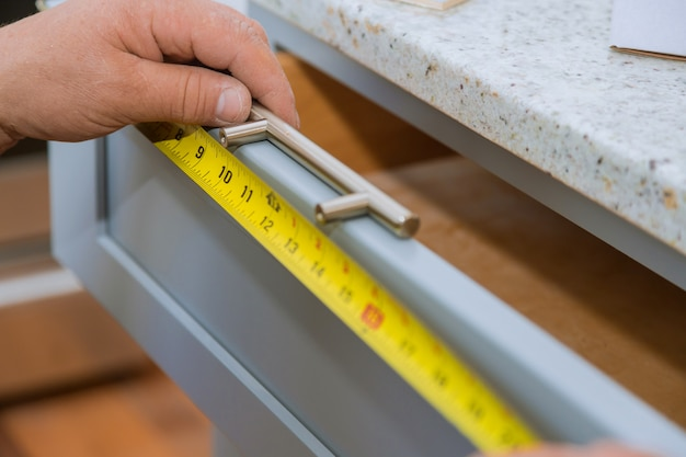 A carpenter is building a man measuring for a drawers in the kitchen Premium Photo