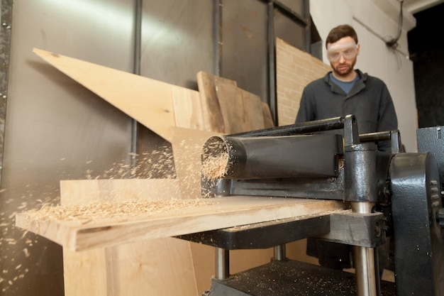 Carpenter joiner working on stationary power planer with wooden planks Free Photo