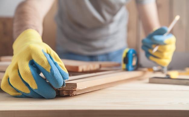 鉛筆で木の板に印をつける大工。 Premium写真